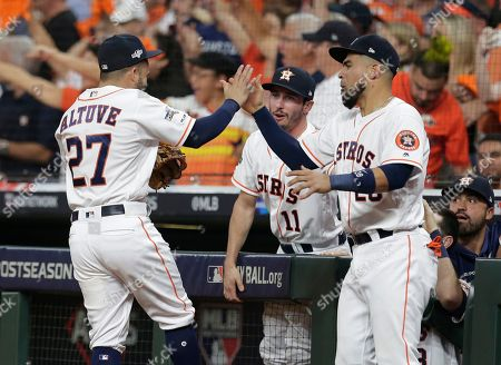 Houston Astros second baseman Jose Altuve (27) celebrates with teammate Robinson Chirinos (28) after he turned a double play against the Tampa Bay Rays in the seventh inning of Game 5 of a baseball American League Division Series in Houston