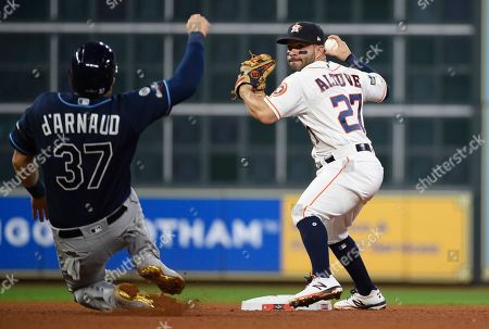 Houston Astros second baseman Jose Altuve (27) turns a double play over Tampa Bay Rays' Travis d'Arnaud (37) during the seventh inning of Game 5 of a baseball American League Division Series in Houston