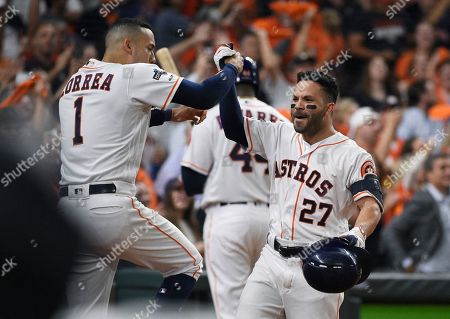 Houston Astros second baseman Jose Altuve (27) celebrates his solo home run against the Tampa Bay Rays with Carlos Correa (1) during the eighth inning of Game 5 of a baseball American League Division Series in Houston