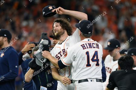 Houston Astros starting pitcher Gerrit Cole (45) celebrates with manager AJ Hinch (14) after the team's win in Game 5 of a baseball American League Division Series against the Tampa Bay Rays in Houston, . Houston won 6-1