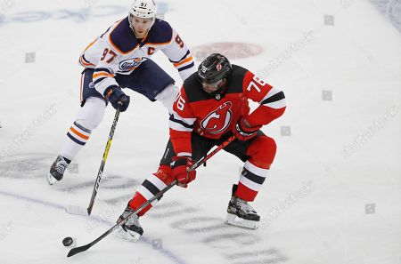 P.K. Subban, Connor McDavid. New Jersey Devils defenseman P.K. Subban (76) corrals the puck in front of Edmonton Oilers center Connor McDavid (97) during the third period of an NHL hockey game, in Newark, N.J