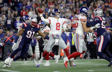 New York Giants quarterback Daniel Jones passes under pressure from New England Patriots defensive end Deatrich Wise, left, and linebacker Kyle Van Noy, right, in the first half of an NFL football game, in Foxborough, Mass