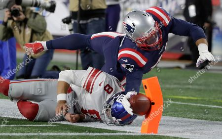 New England Patriots linebacker Kyle Van Noy dives over New York Giants quarterback Daniel Jones to score a touchdown after returning a fumble he recovered in the second half of an NFL football game, in Foxborough, Mass