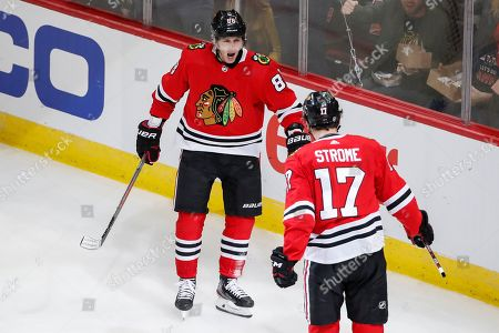 Chicago Blackhawks right wing Patrick Kane, left, celebrates a goal scored by center Dylan Strome, right, during the second period of an NHL hockey game against the San Jose Sharks, in Chicago