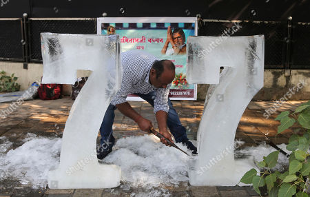 Stock Photo of A fan sculpts the number 77 from ice blocks outside the residence of Bollywood superstar Amitabh Bachchan to celebrate his 77th birthday in Mumbai, . Bachchan turned 77 on Friday