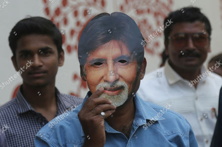 A fan wears the mask of Bollywood superstar Amitabh Bachchan to celebrate his birthday outside his residence in Mumbai, . Bachchan turned 77 on Friday