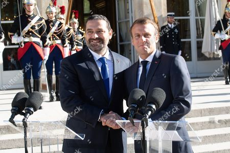 French President Emmanuel Macron and Lebanese Prime Minister Saad Hariri as he welcomes him on arrival at The Elysee Palace in Paris