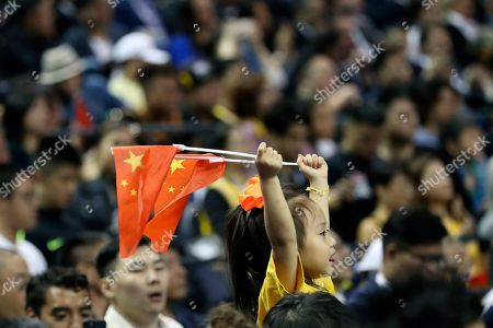 A child holds up two Chinese national flags as she watches a preseason NBA basketball game between the Brooklyn Nets and Los Angeles Lakers at the Mercedes Benz Arena in Shanghai, China. On Thursday the Chinese government stopped NBA Commissioner Adam Silver and the teams from holding news conferences before or after the Lakers-Nets game. That was part of the Chinese response to the rift that started when Houston Rockets general manager Daryl Morey tweeted support for anti-government protesters in Hong Kong and intensified when Silver defended Morey's right to exercise free speech