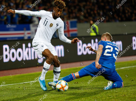 Iceland France Euro 2020 Soccer. France's Kingsley Com­an, left, gets past Iceland's Ari Skulason, right, during a Euro 2020 group H qualifying soccer match between Iceland and France at Laugardalsvollur stadium in Reykjavik, Iceland