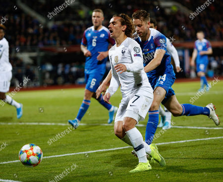 Iceland France Euro 2020 Soccer. France's Antoine Griezmann, left, is challenged by Iceland's Kari Arnason, right, during a Euro 2020 group H qualifying soccer match between Iceland and France at Laugardalsvollur stadium in Reykjavik, Iceland