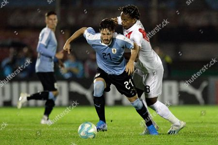Uruguay's Matías Vina, center, is pressured by Andre Carrillo of Peru, during a friendly soccer match, in Montevideo, Uruguay