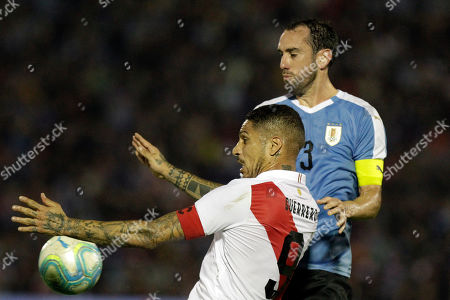 Peru's Paolo Guerrero, front, and Uruguay's Diego Godin, fight for control of the ball during a friendly soccer match, in Montevideo, Uruguay