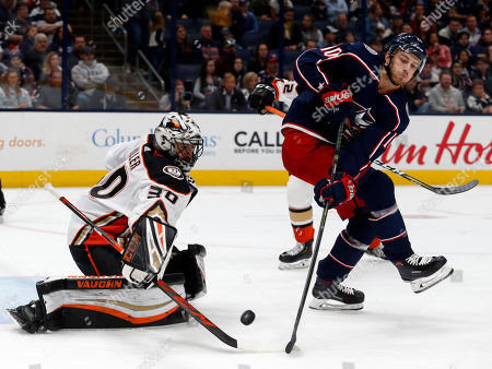 Anaheim Ducks goalie Ryan Miller, left, stops a shot behind Columbus Blue Jackets forward Alexander Wennberg, of Sweden, during the second period of an NHL hockey game in Columbus, Ohio