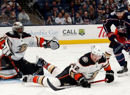 Anaheim Ducks defenseman Josh Manson, center, tries to control the puck in front of Ducks goalie Ryan Miller, left, and Columbus Blue Jackets forward Nick Foligno during the second period of an NHL hockey game in Columbus, Ohio