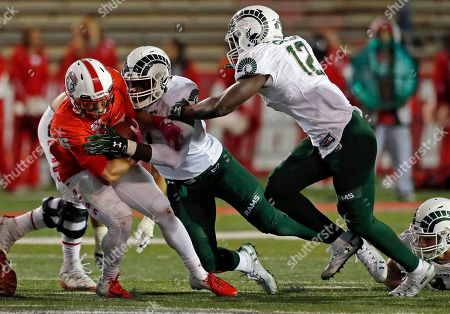 New Mexico running back Bryson Carroll (6) is sacked by Colorado State defensive end Jalen Bates, center, as linebacker Cam'ron Carter (12) closes in during the second half of an NCAA college football game in Albuquerque, N.M. Colorado State won 35-21