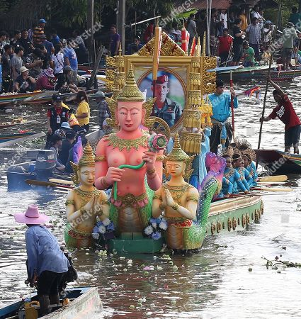 Stock Photo of Decorated boats wind their way down the Bang Pakong river, one carrying a large portrait of Thai King Maha Vajiralongkorn Bodindradebayavarangkun, during celebrate the Rap Bua or Lotus Flower Receiving Festival, in Bang Phli, Samut Prakan province, on the outskirts of Bangkok, Thailand, 12 October 2019. The event is an old tradition in this area, celebrating the end of the Buddhist rain retreat called the Buddhist Lent, when Buddhists come to throw their offerings of lotus flowers on the floating Buddha for merit-making, a day before the official end of lent. The lotus flower is a holy flower because Lord Buddha is said to have walked upon lotus flowers after he was born.