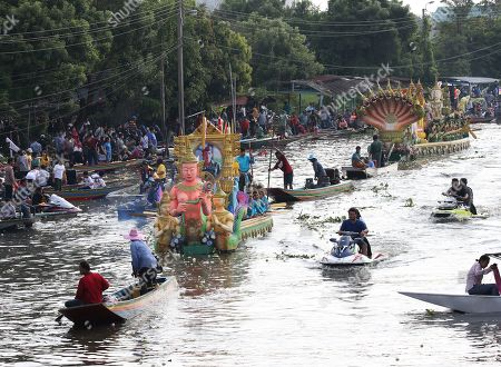 Decorated boats wind their way down the Bang Pakong river, one carrying a large portrait of Thai King Maha Vajiralongkorn Bodindradebayavarangkun, during celebrate the Rap Bua or Lotus Flower Receiving Festival, in Bang Phli, Samut Prakan province, on the outskirts of Bangkok, Thailand, 12 October 2019. The event is an old tradition in this area, celebrating the end of the Buddhist rain retreat called the Buddhist Lent, when Buddhists come to throw their offerings of lotus flowers on the floating Buddha for merit-making, a day before the official end of lent. The lotus flower is a holy flower because Lord Buddha is said to have walked upon lotus flowers after he was born.
