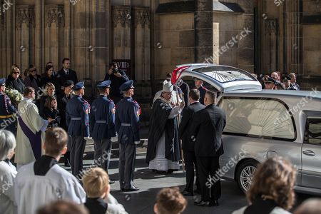 Widow Ivana Gottova (L, rear, with veiled black hat) with her daughters watches Cardinal Dominik Duka (C), Archbishop of Prague, blessing the coffin containing the body of late Czech singer Karel Gott as it is loaded into a hearse after a funeral mass in the Saint Vitus Cathedral at the Prague Castle, in Prague, Czech Republic, 12 October 2019. Karel Gott died at the age of 80 shortly before midnight on 01 October 2019 following a long suffering of cancer. Others are not identified.