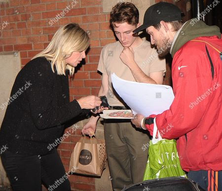 Zoe Ball gives change to a man on the street before nervously getting on a motorcycle