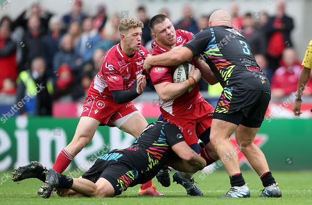 Rob Evans of Scarlets is tackled by Mick Kearney and Alexandru Tarus of Zebre.