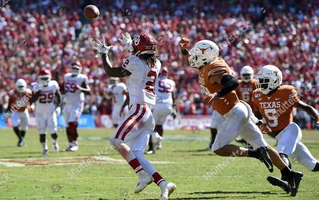 Oklahoma wide receiver CeeDee Lamb (2) hauls in his third touchdown reception in front of Texas defensive back Brandon Jones (19) in the second half of an NCAA college football game at the Cotton Bowl, in Dallas. Lamb finished with 171 receiving yards and three touchdowns as Oklahoma won 34-27