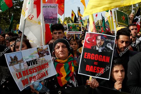 """Protesters carrying a sign reading """"Erdogan=IS"""" referring to Turkish President Recep Tayyip Erdogan take part of a demonstration in support of Kurds being targeted by Turkish forces in Syria, on Republique plaza in eastern Paris, . Demonstrators warned that the offensive could allow Islamic State extremists to resurge. Kurdish forces being targeted by Turkey this week were crucial to the international campaign against IS extremists, who orchestrated several deadly attacks against France"""