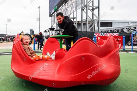 Nascar driver Kyle Larson spins his daughter Audrey as they explore the new facilities and garages at Talladega Superspeedway, in Talladega, Ala