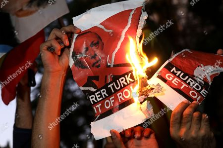 Kurds living in Greece burn a banner depicting Turkish President Recep Tayyip Erdogan, during a rally against Turkey's military action in Syria, in Athens, Greece, . The protesters, waving Kurdish flags as well as placards pledging support for Syria's Kurdish population, chanted slogans condemning Turkey's military action and urged for the withdrawal of Turkish forces