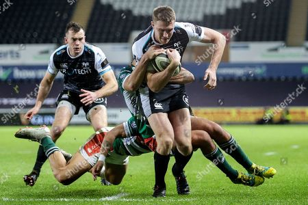 Ospreys vs Benetton Rugby. Ospreys' Tom Williams is tackled by Luca Sperandio and Leonardo Sarto of Benetton