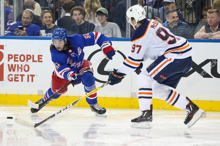 Mika Zibanejad, Connor McDavid. New York Rangers center Mika Zibanejad (93) pass the puck as Edmonton Oilers center Connor McDavid (97) defends during the first period of an NHL hockey game, at Madison Square Garden in New York