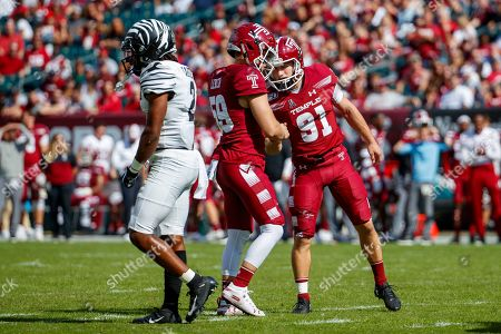 Temple place kicker Will Mobley (91) celebrates the field goal with Cole Lerch (59) as Memphis defensive back T.J. Carter (2) looks on during the first half of an NCAA college football, in Philadelphia. Temple won 30-28