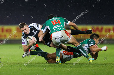Tom Williams of Ospreys is tackled by Ignacio Brex of Benetton Rugby and Leonardo Sarto of Benetton Rugby