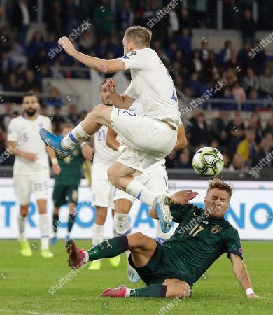 Italy's Ciro Immobile, slides under a tackle fromGreece's Kostas Stafylidis during the Euro 2020 group J qualifying soccer match between Italy and Greece in Rome, Italy
