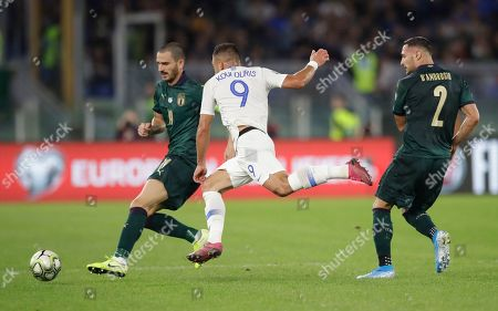 Greece's Efthimis Koulouris, centre, vies for the ball with with Italy's Leonardo Bonucci, left and Italy's Danilo D'Ambrosio during the Euro 2020 group J qualifying soccer match between Italy and Greece in Rome, Italy
