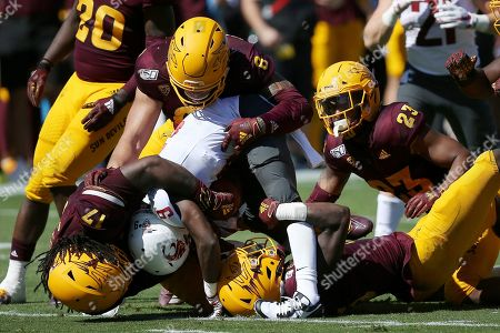 Washington State wide receiver Renard Bell (9) is tackled by Arizona State defensive lineman George Lea (17), linebacker Merlin Robertson (8), linebacker Tyler Whiley (23) and safety Cam Phillips, bottom, during the first half of an NCAA college football game, in Tempe, Ariz