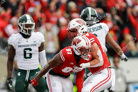 Wisconsin wide receiver Quintez Cephus (87) celebrates a touchdown with teammate Jake Ferguson (84) as Michigan State safety David Dowell (6) Xavier Henderson (3) react during the first half of an NCAA college football game, in Madison, Wis