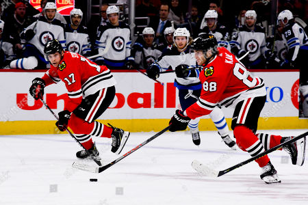 Chicago Blackhawks right wing Patrick Kane (88) and center Dylan Strome (17) move the puck during the first period of an NHL hockey game against the Winnipeg Jets, in Chicago