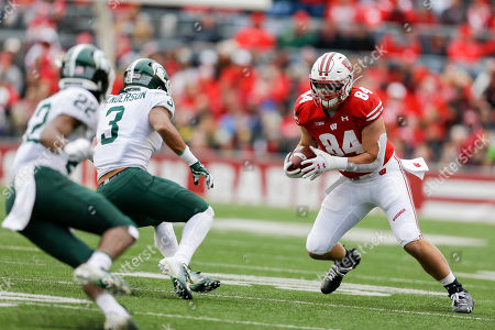 Wisconsin tight end Jake Ferguson (84) abasing Michigan State cornerback Josiah Scott (22) and safety Xavier Henderson (3) during the first half of an NCAA college football game, in Madison, Wis