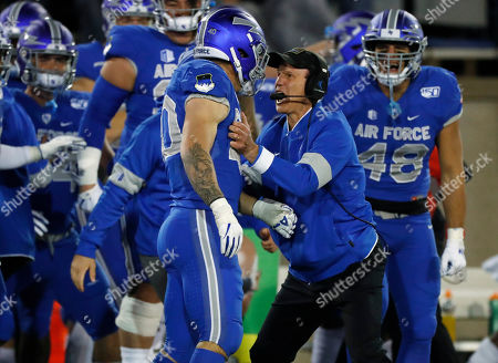 R m. Air Force coach Troy Calhoun, right, congratulates linebacker Kyle Johnson after Johnson intercepted a pass and returned the ball for a touchdown during the second half of the team's NCAA college football game against Fresno State, at Air Force Academy, Colo