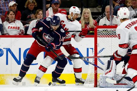 Columbus Blue Jackets' Alexander Wennberg (10), of Sweden, battles with Carolina Hurricanes' Nino Niederreiter (21), of the Czech Republic, for the puck during the first period of an NHL hockey game, in Raleigh, N.C