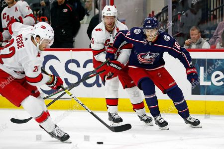 Columbus Blue Jackets' Alexander Wennberg (10), of Sweden, battles with Carolina Hurricanes' Jordan Staal (11) as the Hurricanes Brett Pesce (22) cleans up the puck during the third period of an NHL hockey game in Raleigh, N.C