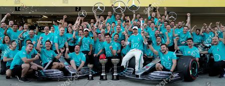 Stock Picture of British Formula One driver Lewis Hamilton (C-L) and Finnish Formula One driver Valtteri Bottas (C-R) of Mercedes AMG GP celebrate with their team members including Team Principal & CEO Toto Wolff (C) and a trademark late Niki Lauda cap after Mercedes won the constructor title after the Japanese Formula One Grand Prix in Suzuka, Japan, 13 October 2019. Mercedes is crowned constructors? champions for the sixth consecutive time.