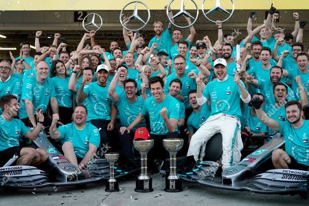 British Formula One driver Lewis Hamilton (C-L) and Finnish Formula One driver Valtteri Bottas (C-R) of Mercedes AMG GP celebrate with their team members including Team Principal & CEO Toto Wolff (C) and a trademark late Niki Lauda red cap after Mercedes won the constructor title after the Japanese Formula One Grand Prix in Suzuka, Japan, 13 October 2019. Mercedes is crowned constructors? champions for the sixth consecutive time.