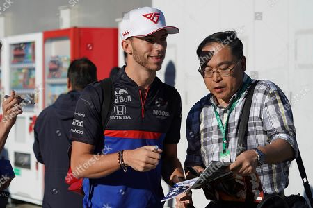 Stock Photo of Toro Rosso driver Pierre Gasly of France signs his autograph for a fan at the paddock of Suzuka Circuit ahead of the Japanese Formula One Grand Prix in Suzuka, central Japan