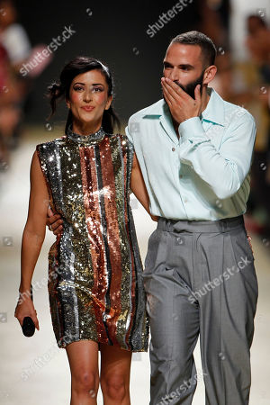Stock Picture of Portuguese fashion designer Luis Carvalho (R) accompanied by Portuguese Fado singer Ana Moura (L) appears on the catwalk after presenting his creations on the last day of Lisbon Fashion Week at Campo Santa Clara in Lisbon, Portugal, 13 October 2019.