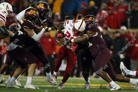 Nebraska running back Maurice Washington tries to break through the tackle of Minnesota linebacker Thomas Barber during the second half of an NCAA college football game, in Minneapolis