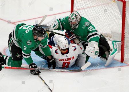 Jamie Oleksiak, Anton Khudobin, Alex Ovechkin. Dallas Stars' Jamie Oleksiak (2) and goaltender Anton Khudobin (35) fall onto Washington Capitals left wing Alex Ovechkin (8) on a shot attempt by Ovechkin in the third period of an NHL hockey game in Dallas