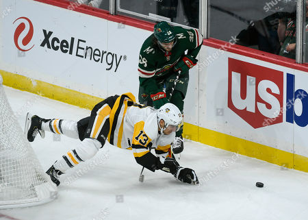 Pittsburgh Penguins winger Brandon Tanev (13) is tripped by Minnesota Wild winger Ryan Hartman (38) during the first period of an NHL hockey game, in St. Paul, Minn