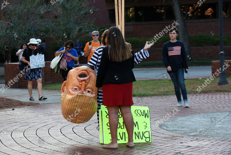 A protester holds a Donald Trump costume head while giving an interview before a speech by Donald Trump, Jr. and his girlfriend, Kimberly Guilfoyle, who appeared at the University of Florida campus and spoke to a capacity crowd of about 850 students in what was billed as a keynote presentation.
