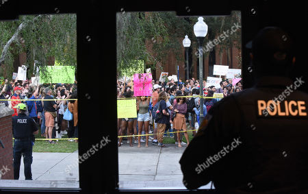 Police watch as demonstrators protest before a speech by Donald Trump, Jr. and his girlfriend, Kimberly Guilfoyle, who appeared at the University of Florida campus and spoke to a capacity crowd of about 850 students in what was billed as a keynote presentation.